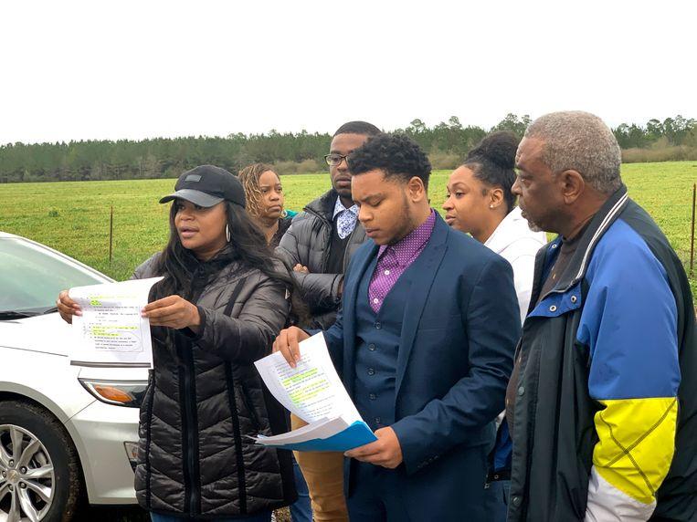 Familieleden van Woods doen donderdag nog een poging de veroordeling tegen te gaan. De zus van Nathaniel (links in beeld) houdt een transcript omhoog waaruit Woods' onschuld zou blijken. Beeld AP