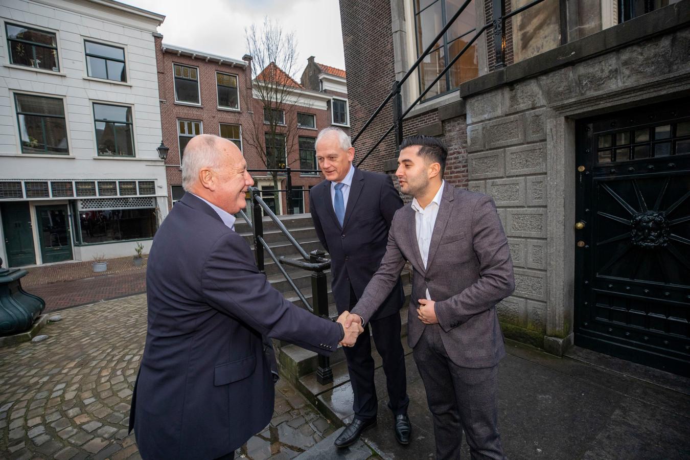 Dogukan Ergin, fractievoorzitter van Denk Schiedam, ontvangt de Amerikaanse ambassadeur Pete Hoekstra. Burgemeester Cor Lamers kijkt toe.