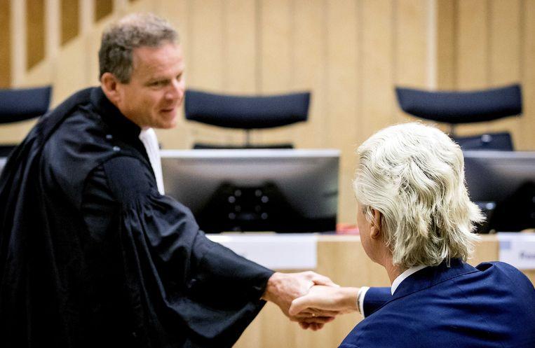 Geert Wilders schudt de hand van advocaat-generaal Gerard Sta voorafgaand aan de voortzetting van het hoger beroep in de strafzaak tegen de PVV-leider in de rechtszaal van Justitieel Complex Schiphol. Beeld ANP