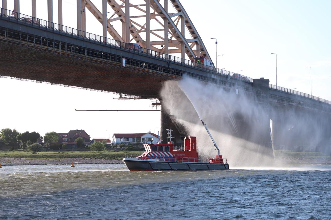 Met behulp van een blusboot probeert de brandweer het vuur onder controle te krijgen.