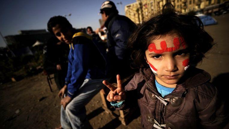 Een Egyptisch meisje met het woord 'Allah' op haar voorhoofd, geeft het vredesteken. Beeld afp