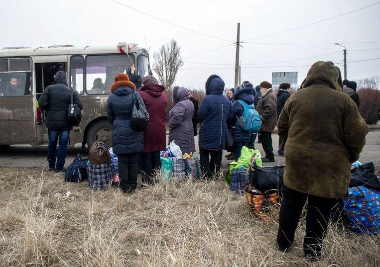 Vluchtelingen uit Debaltseve staan in de rij voor een bus die hen uit het conflictgebied haalt