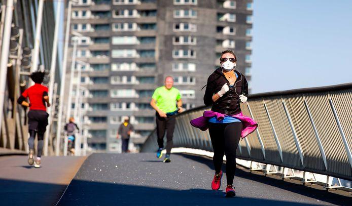 Hardlopers lopen over de Erasmusbrug op de dag dat de marathon Rotterdam zou plaatsvinden. Door de mondiale uitbraak van het nieuwe coronavirus besloot de organisatie het evenement uit te stellen. ANP BART HOOGVELD