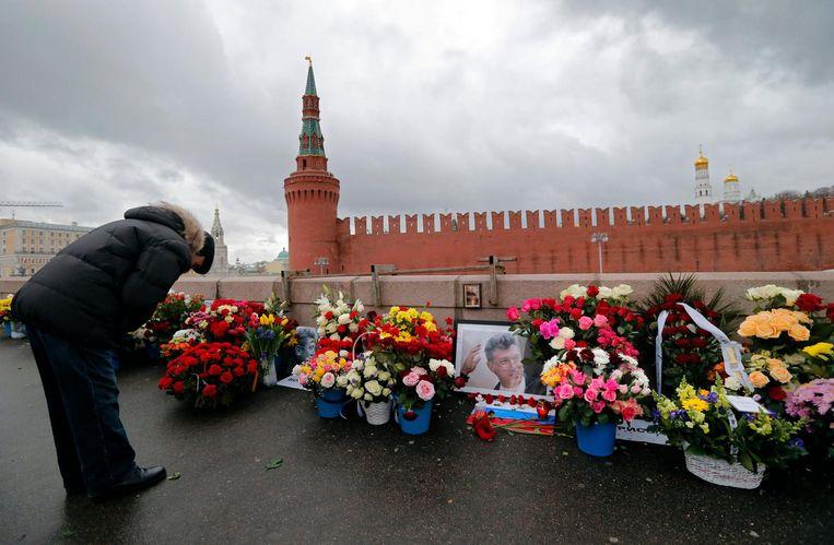 Een man legt bloemen op de plek waar Boris Nemtsov werd vermoord, twee jaar na dato. Beeld epa