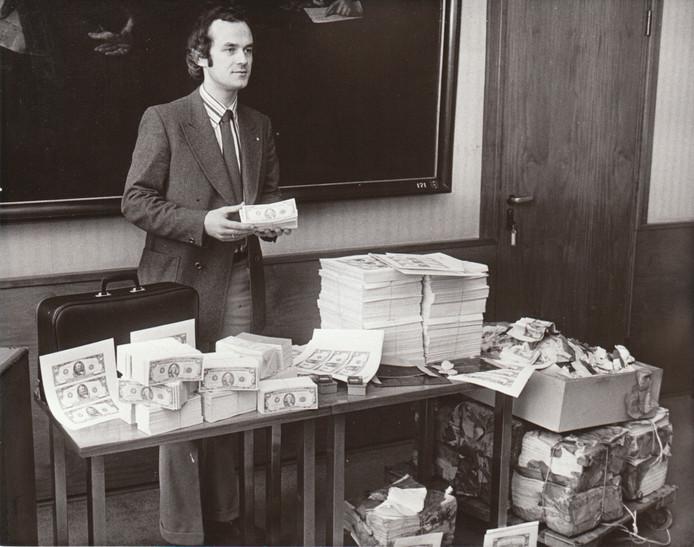 Bende valsemunters opgerold. Zes mannen hebben voor 1,5 miljoen aan valse dollarbiljetten gemaakt. De biljetten kwamen voor een deel uit Waalre. Hoofdinspecteur Sietsma leidde het onderzoek. De stapel rechts op de foto is uit het water gehaald (29-3-74).