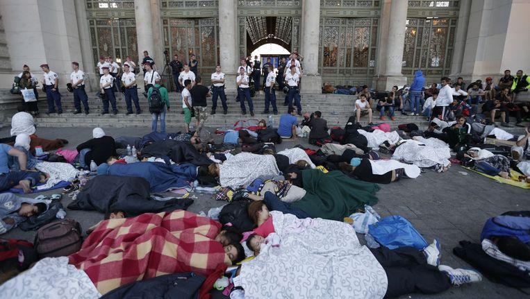 Migranten slapen voor de ingang van het Keletistation in Boedapest. Beeld ap