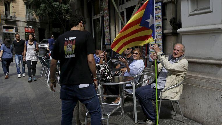 Een man houdt op een terrasje een vlag vast die symbool staat voor Catalaanse onafhankelijkheid. Beeld reuters