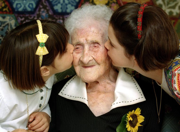 Twee meisjes kussen Jeanne Calment in 1995, ze is dan 120 jaar oud. Beeld REUTERS