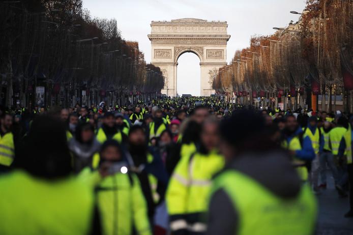 Gele hesjes lopen over de Champs Elysees richting de Place de la Concorde, waar ze worden tegengehouden.