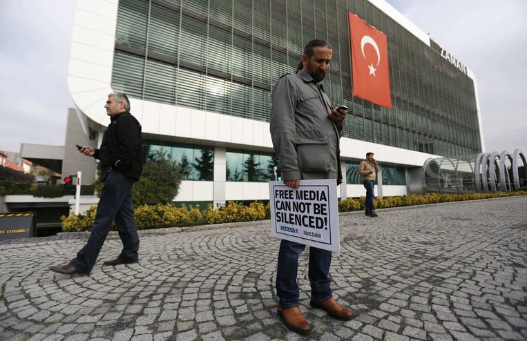 Een journalist voor het kantoor van de Turkse krant Zaman houdt een bord vast met de tekst: 'Free media cannot be silenced' Beeld reuters