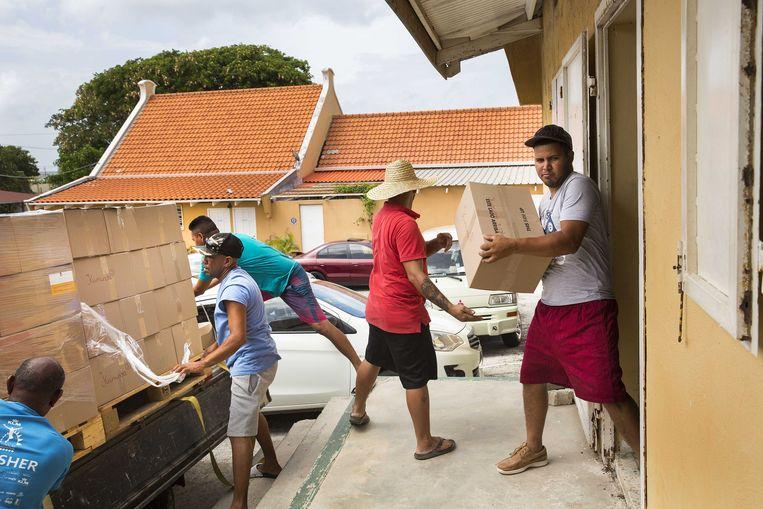 Het Rode Kruis zorgt voor voedselpakketten, hygiënepakketten en pakketten met babyspullen in Willemstad, voor mensen die hun baan kwijt zijn door de coronacrisis.  Beeld ANP