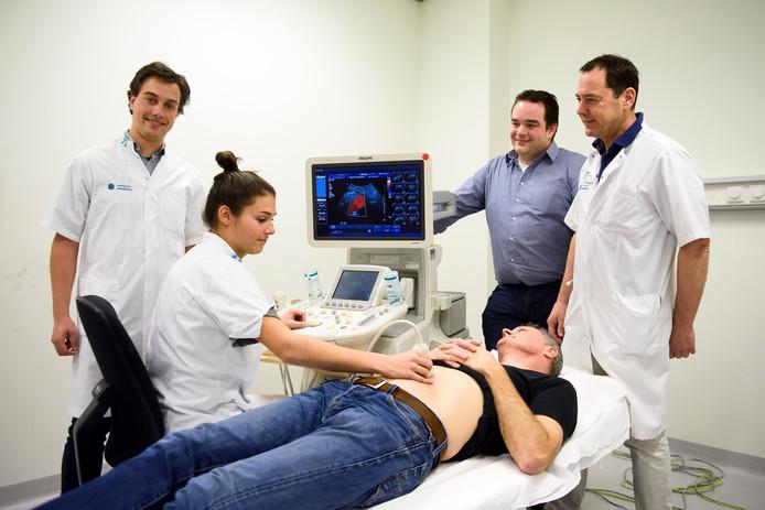 Van links naar rechts: Emiel van Disseldorp, vaatassistente Lisanne Passier, co-promotor Richard Lapota en promotor Marc van Sambeek. Op de behandeltafel ligt een ziekenhuismedewerker als model.