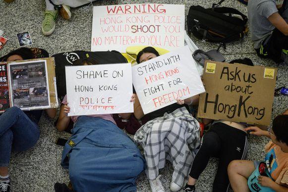 Demonstranten houden borden omhoog terwijl ze de luchthaven van Hongkong bezetten.