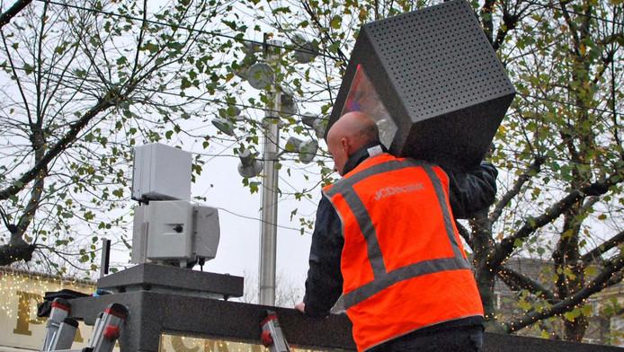 Een installateur plaatst een kleine zendmast in een abri op het Rembrandtplein.