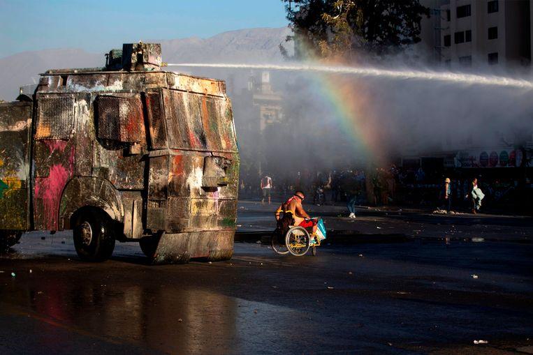 Een demonstrant in een rolstoel vlucht voor een spuitwagen van de Chileense politie. Het is sinds oktober onrustig in de Chileense hoofdstad en omstreken vanwege protesten tegen de sociale crisis in het Zuid-Amerikaanse land.