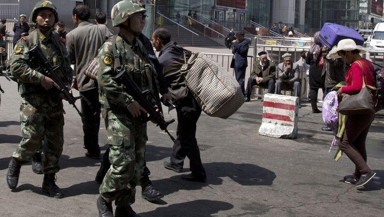 Zwaar bewapende militairen patrouilleren in Urumqi na een eerdere aanslag op het station. Beeld ap