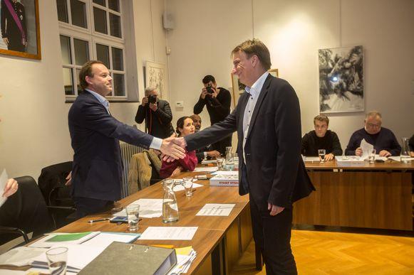 Yves Ghequiere (rechts) schudt de hand van Damien Thiéry tijdens de installatievergadering. Voorlopig bekommert de voorgedragen burgemeester zich om 25 bevoegdheden.