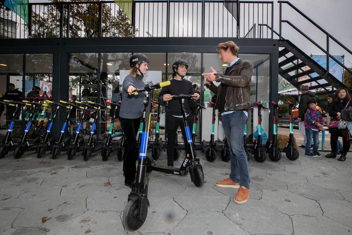 Marijn Berk (rechts) van e-step producent Dott, geeft uitleg over het gebruik aan Robert uit Eindhoven en zijn vriendin Caroline uit Rotterdam.