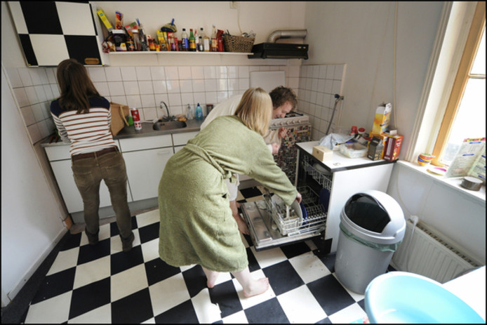 Studenten ruimen op in de keuken.
