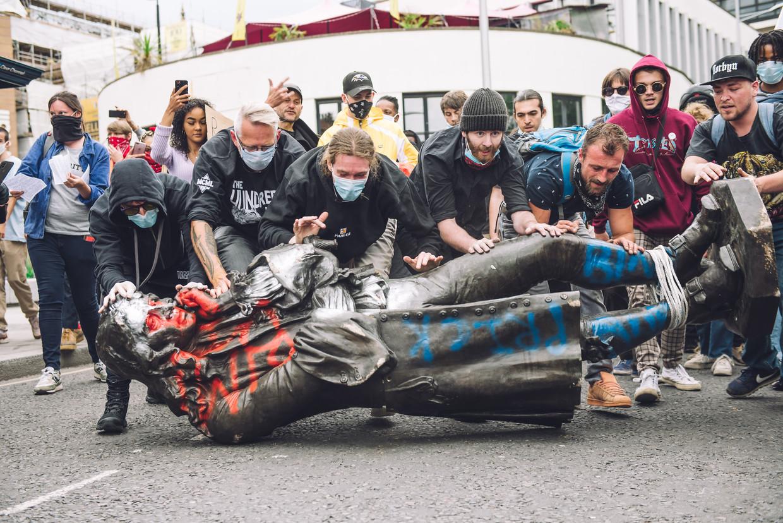 In Bristol rollen demonstranten het beeld van slavenhandelaar Edward Colston naar de rivier de Avon.  Beeld Getty Images