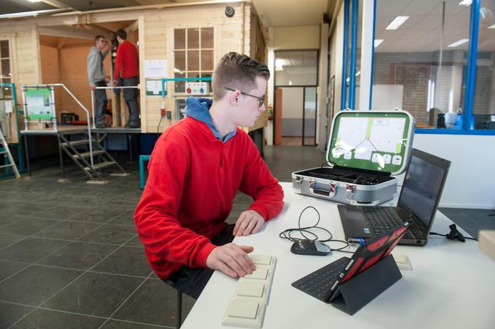 Bram Brouwer demonstreert de simulatiekoffer. Achter hem zijn Martijn van de Velde en Lars Steenpoorte aan het werk.