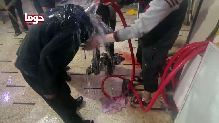 Een still uit video, waarop een vrijwilliger een man afspoelt met water na de vermeende chemische aanval in Douma. Beeld AFP
