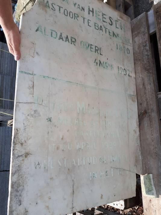 De verweerde plaat zoals die de afgelopen eeuw op het priestergraf van de Batenburgse Calvarieberg te zien was. De originele uit 1874 zat verborgen aan de binnenzijde.