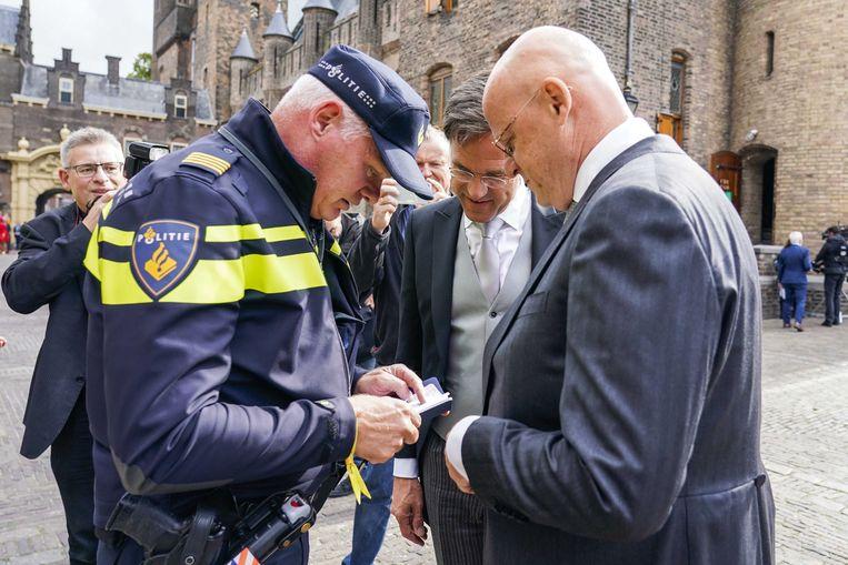 Ferdinand Grapperhaus in gesprek met een politieagent bij de Ridderzaal op Prinsjesdag. Bij de politie is vergrijzing een groot probleem.  Beeld ANP