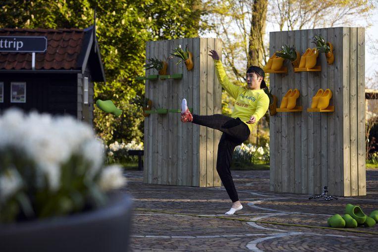 Fotomodel en zanger Yilun Sheng voert een kunststukje uit met klompen. Beeld Jan Dirk van der Burg