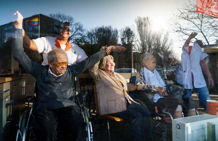 Drie volkszangers uit het Westland, Ronnie Ronaldo, John Dame en Mark Verkade, zingen voor de bewoners van verpleeghuis Wijndaelercentrum in de Haagse wijk Loosduinen. De zangers besloten spontaan om een tour langs vijf verpleeghuizen te maken om de bejaarden een hart onder de riem te steken tijdens de coronacrisis.  Beeld ANP