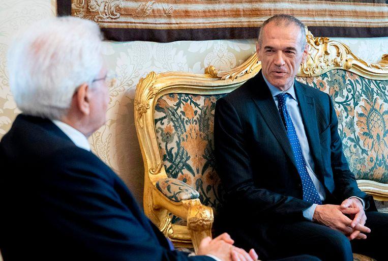 De Italiaanse president Sergio Mattarella (L) ontmoet Carlo Cottarelli (R). Beeld null
