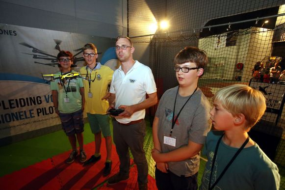 Lesgever Thomas Demeyer (links) toont de kinderen hoe ze een drone moeten besturen.
