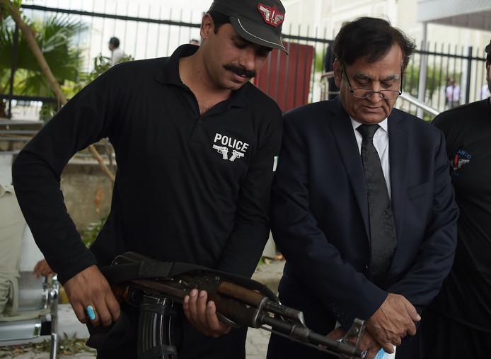 Saif-ul-Malook verlaat onder politiebegeleiding het gerechtshof in Pakistan. De advocaat van Asia Bibi is inmiddels naar Nederland gevlucht.