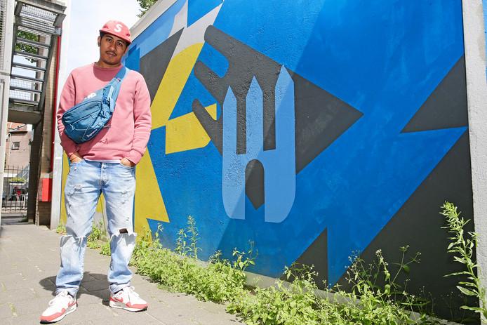 Aziz Lessy bij zijn  muurschilderingen bij Brouwerslaken in de binnenstad.