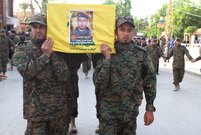 Leden van Hezbollah dragen de kist met een omgekomen strijder tijdens een begrafenis in Baalbek. Beeld reuters