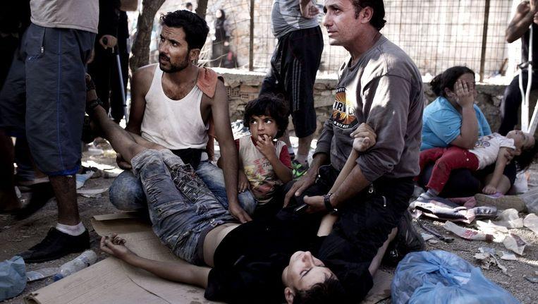 Een vluchteling is flauwgevallen terwijl hij in de rij stond om geregistreerd te worden in Mytilene, op het Griekse eiland Lesbos. Beeld afp
