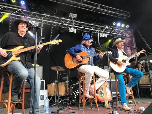 De drie bandleden van het eerste uur op het podium.