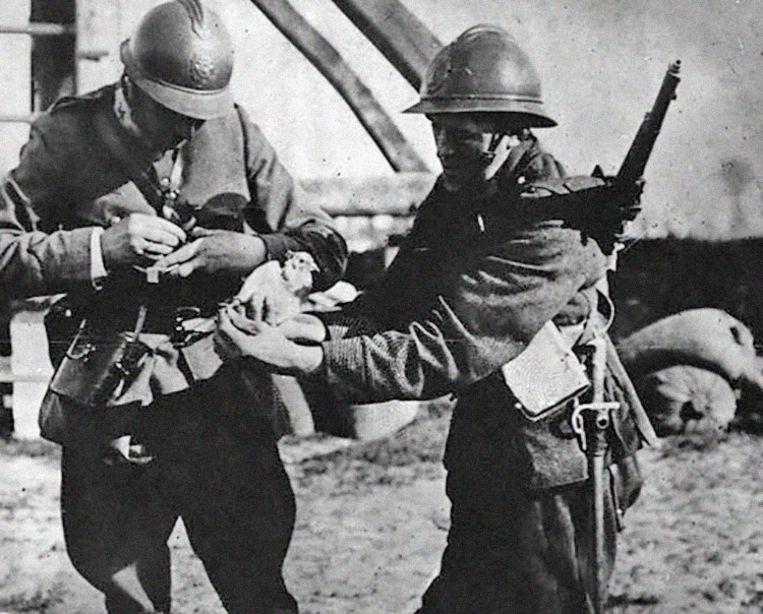 Twee soldaten bevestigen een boodschap aan een postduif tijdens WO I.