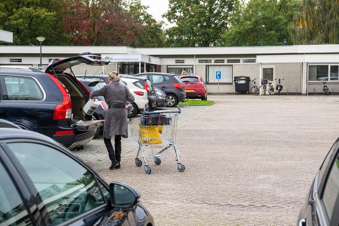 Een vrouw laadt haar boodschappen op de parkeerplaats van het gezondheidscentrum in haar auto en laat het winkelwagentje vervolgens staan.