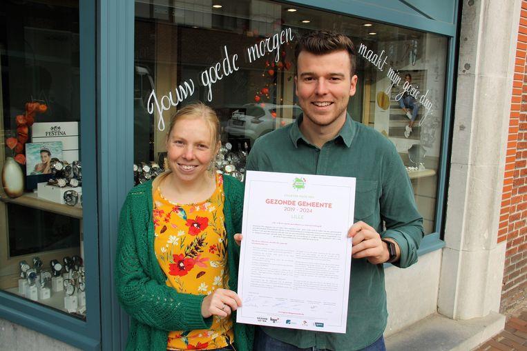Chiel Danckers en Lieselot Wynants met het pas ondertekende charter voor de etalage van juwelier Walter Peeters die deelnam aan de campagne 'Spreuken in het straatbeeld'.