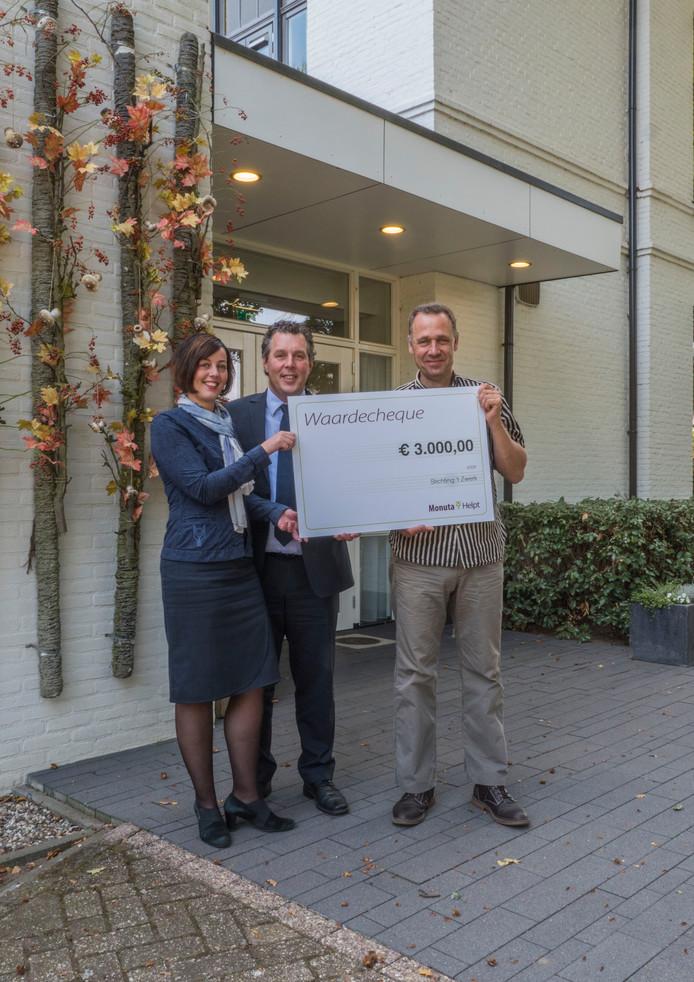 Uitvaartverzorgers Ellen Wezendonk en Andre Zaalmink geven de cheque aan Jos Spijkers.