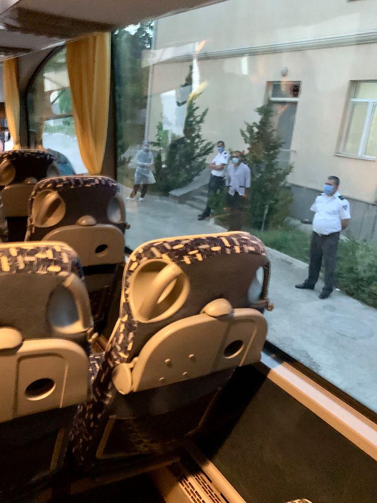 De passagiers worden onder politie-escorte  naar het quarantaine-hotel in Tbilisi gebracht. Beeld Ton Damen