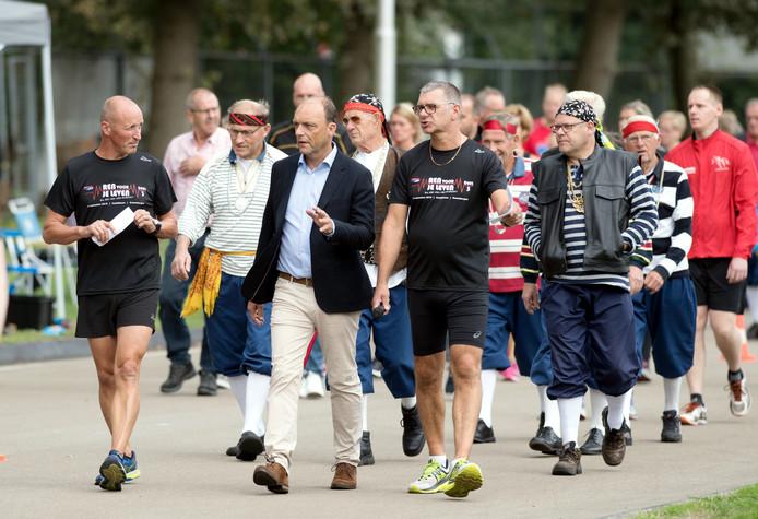 Initiatiefnemer Henk Meppelink (l) wandelt na het startsein naast burgemeester Peter Snijders, op de voet gevolgd door de Sjompiesingers.
