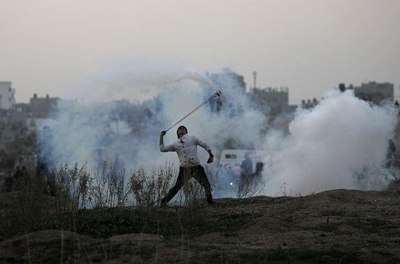 Een Palestijn gooit Israelisch traangas terug bij de grens tussen Israël en de Gazastrook.
