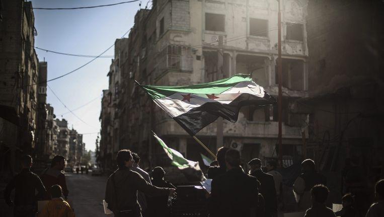 Een Syriër zwaait met de nationale vlag in een protest tegen de luchtaanvallen. Beeld ANP