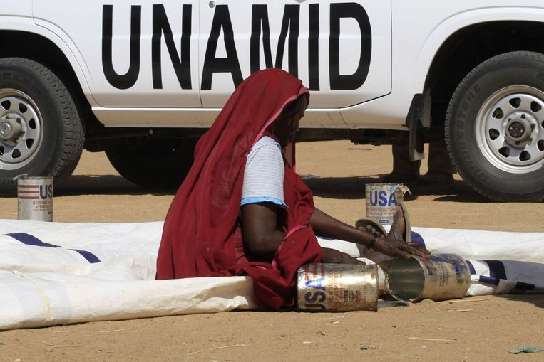 Een vrouw in Sudan zit op een weg voor een auto van de VN. Beeld afp