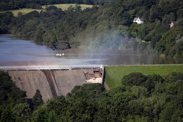 Een Chinook-helikopter laat zandzakken vallen op de Todbrook Reservoir-dam bij de Engelse plaats Whaley Bridge. Na hevige regenval dreigde de dam te bezwijken. De  1500 inwoners van het dorp in het Peak District werden daarom donderdagavond uit voorzorg geëvacueerd.  Beeld REUTERS