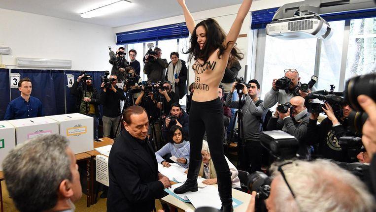 Activiste van 'Femen' protesteert in het stembureau tegen oud-premier Silvio Berlusconi Beeld epa