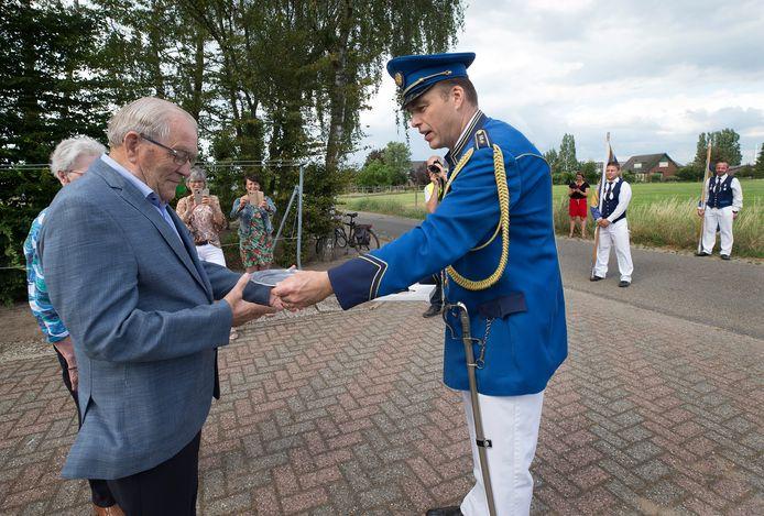 Jan Gasseling ontvangt het herdenkingsbord van voorzitter Richard Giezen van schutterij Sint Jan uit Kilder.