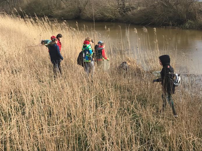 Zo'n vijftien mensen, vooral kinderen, doen mee met de schoonmaakactie in de rivierkade van de Donge en Amer.